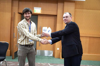 Максим Бадаев (справа), руководитель проекта ЗАО «Нанософт», вручает подарок от спонсора конференции