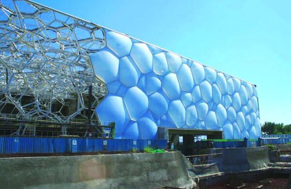 Монтаж стен из пузырьков при строительстве водного стадиона. Слева видны открытые конструкции несущего каркаса